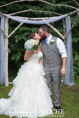 a kiss in front of a birch tree wedding arch