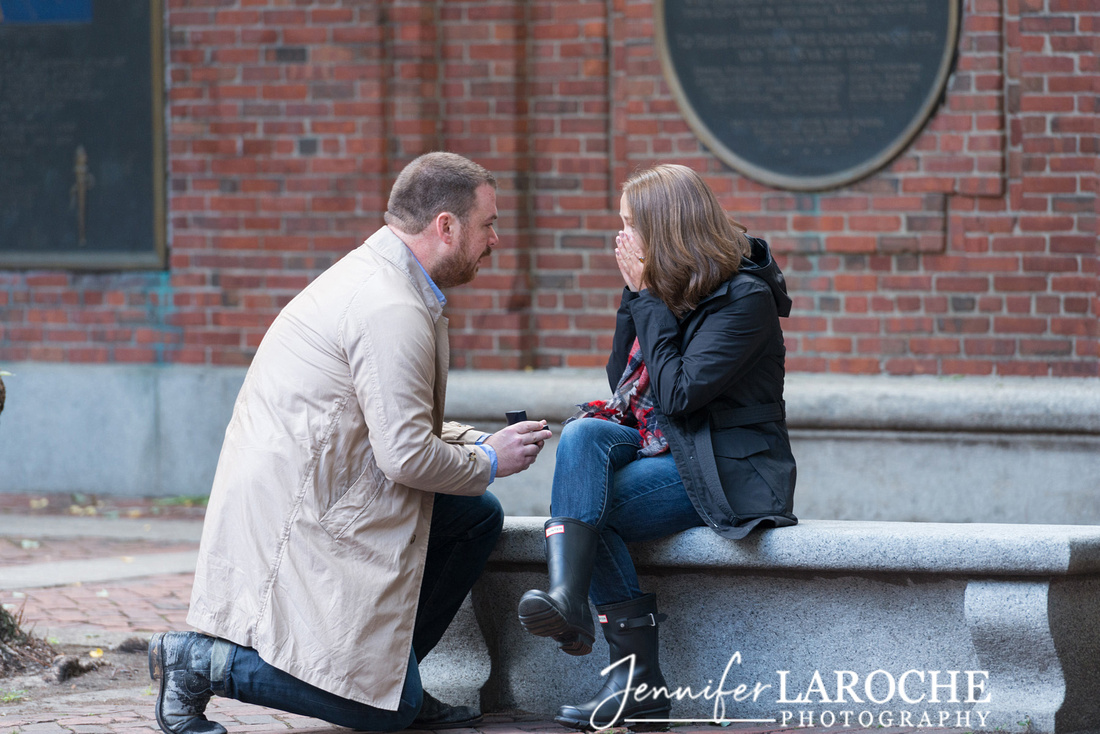 boston man on bended knee proposing to his girlfriend