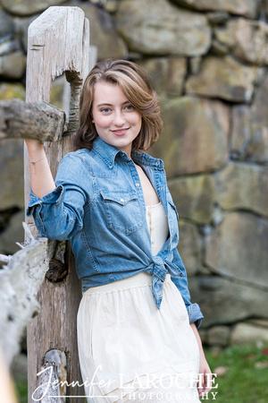 vertical-senior-portrait-girl-leaning-on-fence